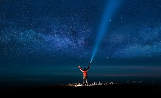 Nachthemel met melkweg en silhouet van een staande gelukkige man met klassiek blauw licht.