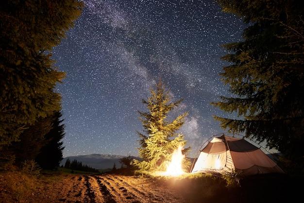 Nachtkamperen in de bergen onder de sterrenhemel en de melkweg