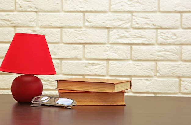 Nachtlamp en boeken op het bureau op witte bakstenen muurachtergrond