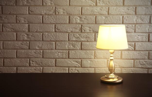 Nachtlamp op het bureau op witte bakstenen muurachtergrond