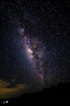 Nachtlandschap met de melkweg en licht van huis bij bergen in thailand