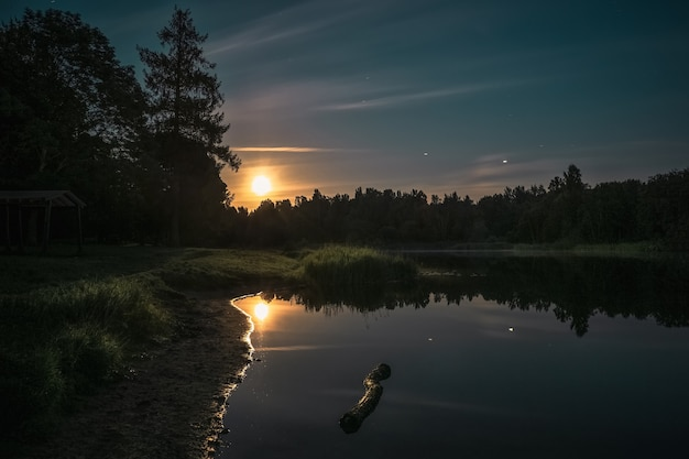 Nachtlandschap met de weerspiegeling van de maan in het meer.