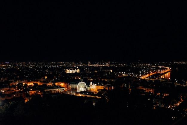 Nachtlandschap van de stad kiev gloeien met lichten vanaf een hoog punt