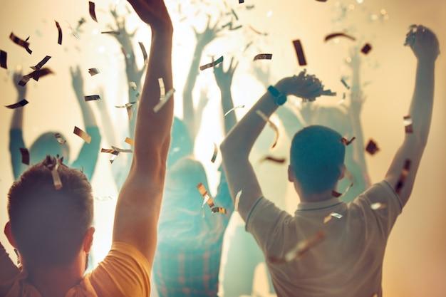 Nachtleven en disco concept. jongeren dansen in de club of buiten in het zonlicht. geluk, vakantie, jeugdconcepten. vrouwelijke en mannelijke handen en silhouetten in rook