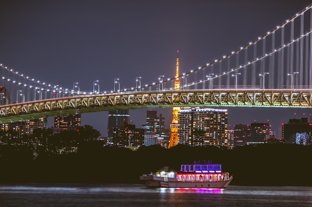 Nachtmening regenboogbrug en de toren van tokyo. de cruise is varen in de baai van tokyo, odaiba bij nacht, japan