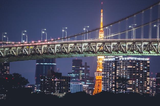Nachtmening regenboogbrug en de toren van tokyo. tokyo city skyline-achtergrond van de baai van tokyo odaiba, japan