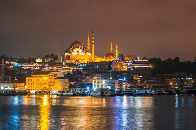 Nachtmening van cityscape suleymaniye moskee van istanboel met drijvende toeristenboten in bosphorus