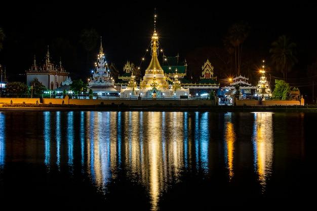 Nachtmening van mooie boeddhistische tempel dichtbij meerwater, thailand