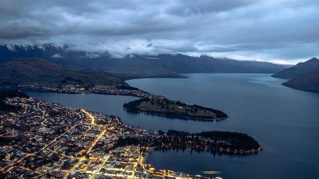 Nachtpanorama van de stad aan de oever van het meer, omringd door bergen queenstown, nieuw-zeeland