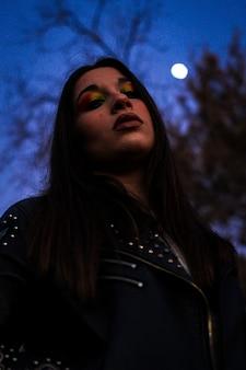 Nachtportret van een serieus mooi meisje in make-up die met blauwe nachtachtergrond in het veld staart