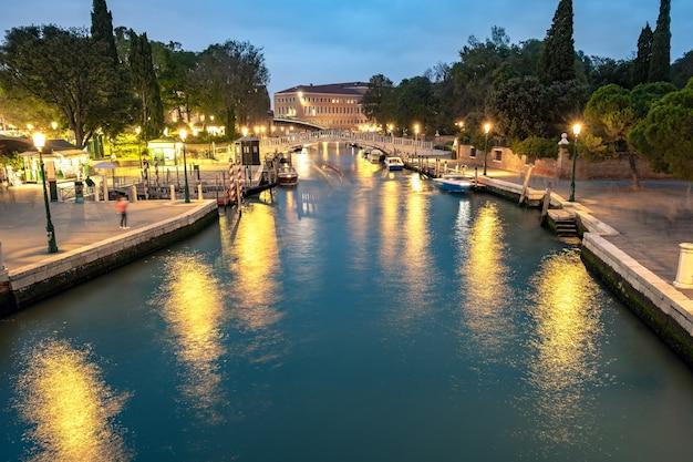Nachtscène in venetië, italië met verlichte oude gebouwen en reflecties in kanaalwater.