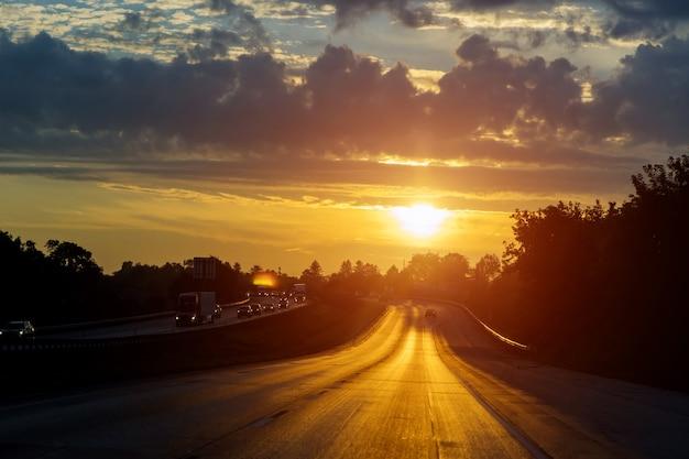 Nachtverkeer, auto's op snelwegweg op zonsondergangavond