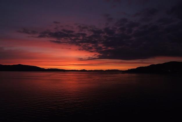 Nachtzeegezicht in bergen, noorwegen. zee- of oceaanwater onder donkere magenta hemel op natuurlijke achtergrond. natuur, ecologie, reislust, vakantieconcept