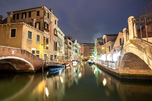 Nachtzicht op verlichte oude gebouwen, drijvende boten en lichtreflecties in kanaalwater in venetië, italië.