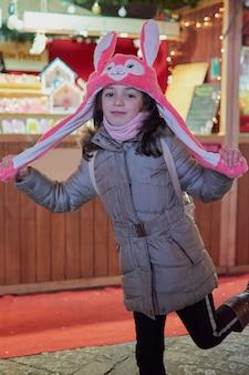 Nachtzicht van een lachend meisje met een roze hoed met verlichte oren met kerstmis in toledo, spanje