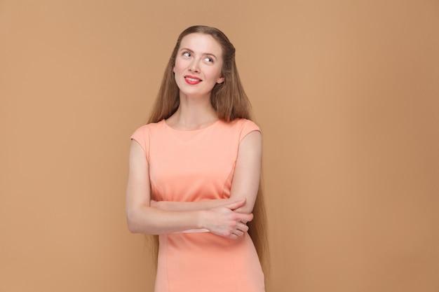 Nadenken, dromen mooie vrouw wegkijken. portret van emotionele schattige, mooie vrouw met make-up en lang haar in roze jurk. indoor studio opname, geïsoleerd op lichtbruine of beige achtergrond.