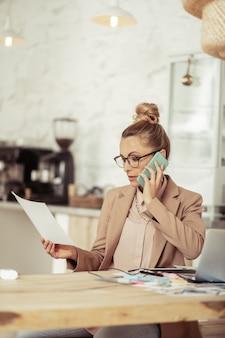 Nadenken over details. geconcentreerde modestyliste die haar schetsen vasthoudt en aan de telefoon met de klant praat.