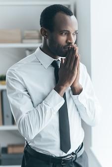 Nadenken over nieuw project. knappe jonge afrikaanse man die hand in de buurt van het gezicht geklemd houdt en wegkijkt terwijl hij in een creatief kantoor staat Premium Foto