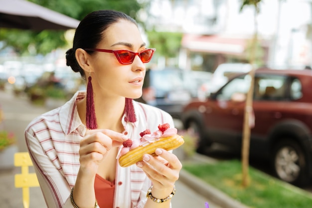 Nadenken tijdens het eten. nieuwsgierige jonge vrouw met rode bril en bedachtzaam in de verte kijken tijdens het buiten eten van een heerlijke eclair