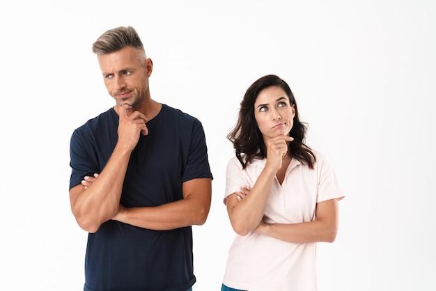Nadenkend aantrekkelijk paar met een casual outfit die geïsoleerd over een witte muur staat en wegkijkt