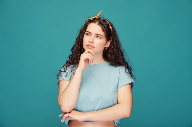 Nadenkend aantrekkelijke jonge vrouw in haar sjaal met kin terwijl wegkijken op blauw