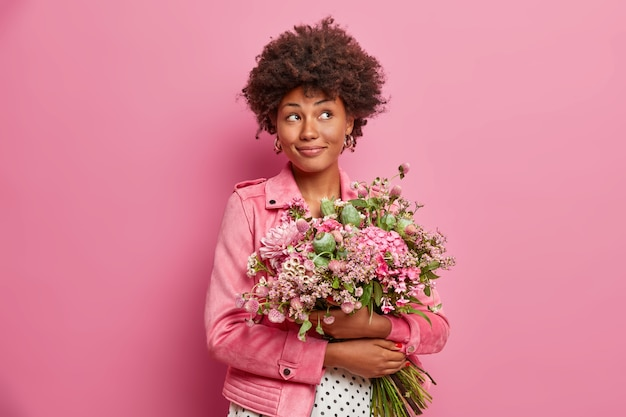 Nadenkend afro-amerikaanse vrouw met mooi boeket bloemen, gekleed in modieuze kleding,