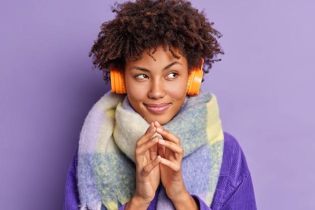 Nadenkend afro-amerikaanse vrouw steekt vingers shemes iets tijdens het luisteren naar favoriete muziek draagt stereokoptelefoon op oren sjaal om nek.