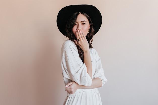 Nadenkend aziatische vrouw die in zwarte hoed camera bekijkt. studio shot van betoverend japans model geïsoleerd op beige achtergrond.