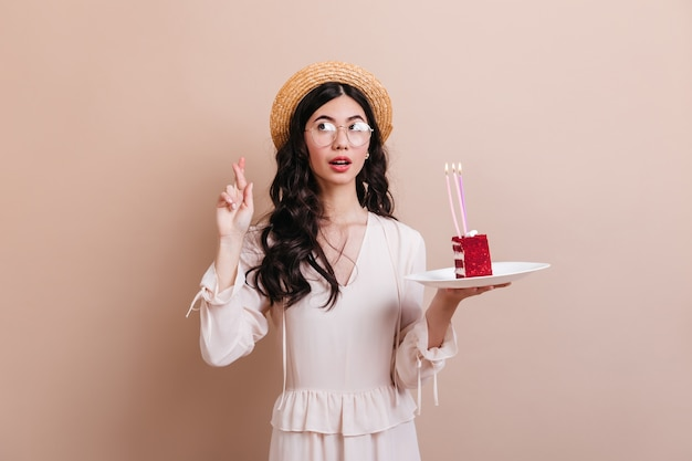 Nadenkend aziatische vrouw die verjaardagswens maakt. studio die van mooi krullend chinees model met cake is ontsproten.