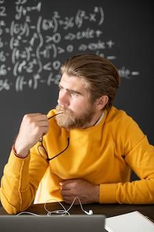 Nadenkend bebaarde leraar in gele pullon denken aan een nieuwe lezing voor laptop terwijl ze een korte pauze hebben tussen online lessen