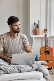 Nadenkend bebaarde man thuis poseren tijdens het werken