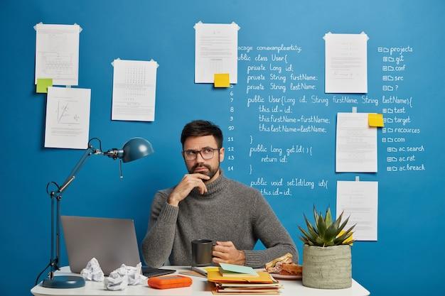 Nadenkend bebaarde werknemer in casual coltrui, denkt aan bedrijfsinformatie, mok thee houdt, poses in coworking space, zit voor laptop tegen blauwe achtergrond.