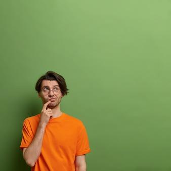 Nadenkend besluiteloze volwassen man kijkt naar boven en houdt de vinger bij de mond, gekleed in een casual oranje t-shirt, poseert tegen de groene muur met kopie ruimte voor uw promotie