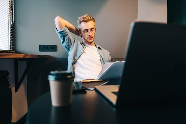 Nadenkend blanke man aan het werk met laptop thuis kantoor en kijken op papieren documenten, rekeningen berekenen