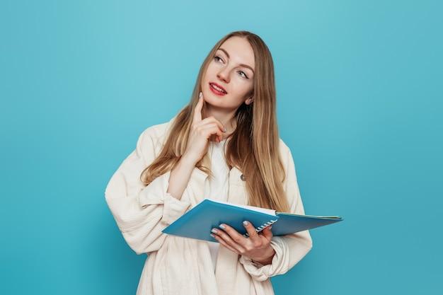 Nadenkend blond studentenmeisje dat een open oefenboek houdt en ruimte wil kopiëren die op blauwe muur wordt geïsoleerd