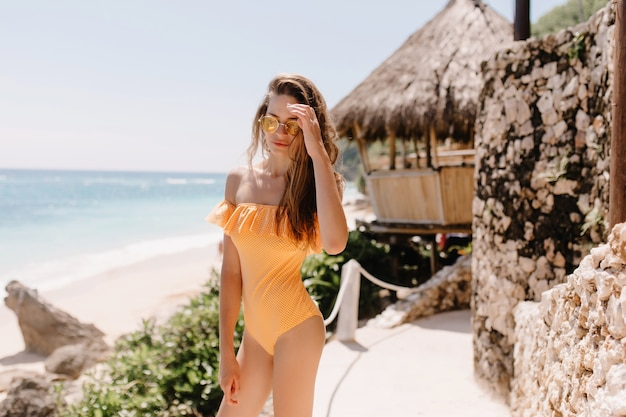 Nadenkend bruinharige meisje in oranje zwembroek poseren voor bungalow. buiten schot van vrij witte jonge dame in zonnebril chillen in ocean resort.