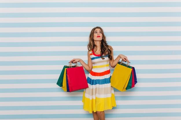 Nadenkend brunette met felle lippenstift vormt met grappig gezicht na het winkelen. vrouwelijke full-length foto op lichte muurmuur