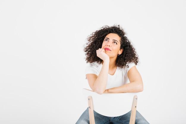 Nadenkend brunette op stoel