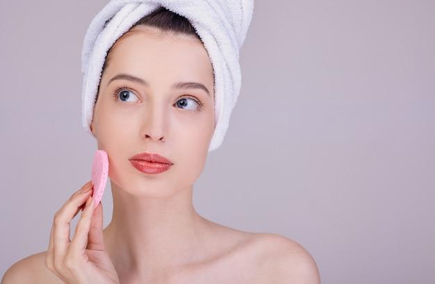 Nadenkend brunette reinigt haar gezicht met een spons