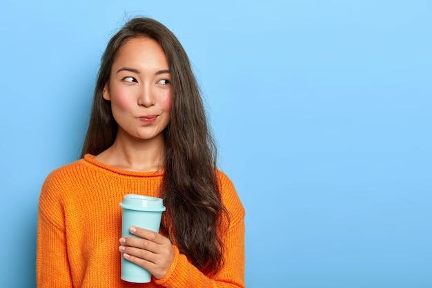 Nadenkend brunette vrouw portemonnees lippen, kijkt bedachtzaam opzij, houdt afhaalkoffie vast, neemt beslissing in gedachten, plant haar dag, draagt oranje trui, staat over blauwe muur