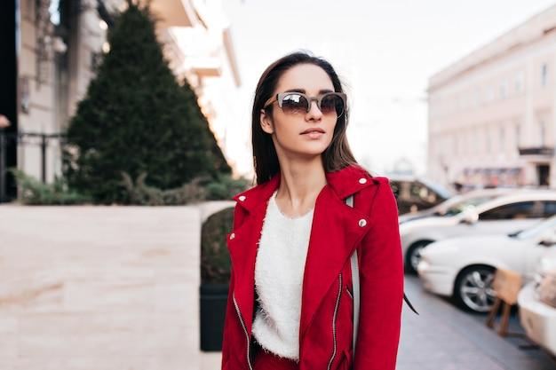 Nadenkend brunette vrouw rondkijken tijdens het lopen op straat