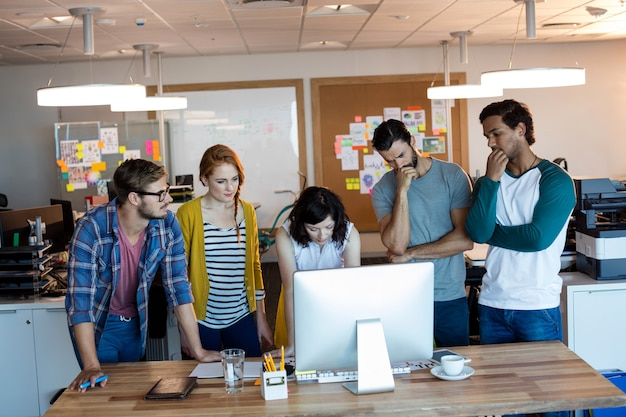 Nadenkend creatief commercieel team dat aan desktoppc samenwerkt