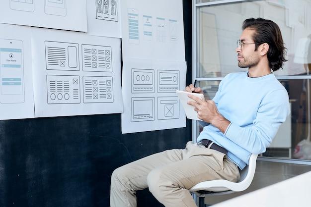 Nadenkend creatieve ontwerper die in glazen bord met schetsen bekijkt en aantekeningen maakt over het ontwerp van de gebruikersinterface