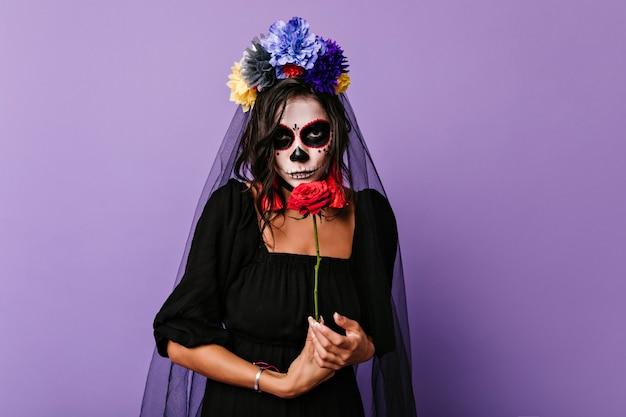 Nadenkend dode bruid poseren met rode bloemen. binnen schot van elegante blanke vrouw in zombiekostuum partij voorbereiden.