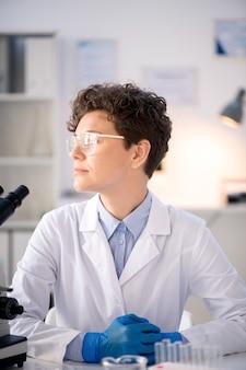 Nadenkend doelgerichte curly-haired viroloog in laboratoriumjas en handschoenen zit aan bureau in modern laboratorium en wegkijken