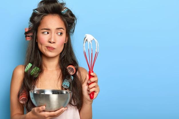 Nadenkend donkerharige dame bezig met het koken van dessert, houdt garde en kom vast, mengt wit ei om room te maken, draagt haarkrulspelden, nachtkleding, heeft besluiteloze gezichtsuitdrukking, poseert over blauwe muur