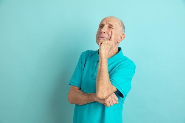 Nadenkend, dromend. kaukasische senior man portret op blauwe studio.