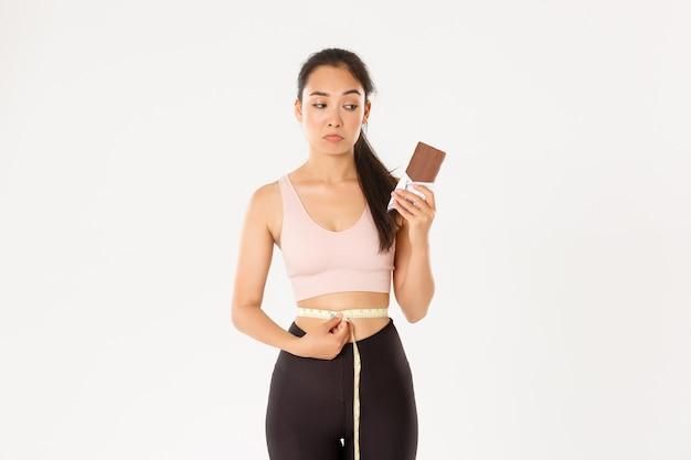 Nadenkend en besluiteloos aziatisch meisje kijkt somber over lichaamsgewicht, meet taille maar kijkt naar chocoladereep, peinzend,