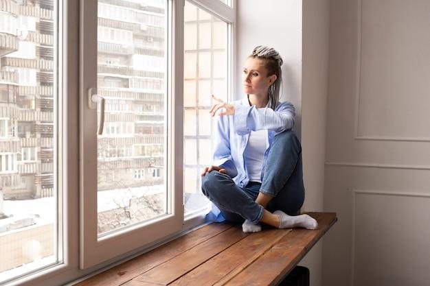Nadenkend en dromend meisje kijkt uit het raam terwijl ze op de vensterbank zit