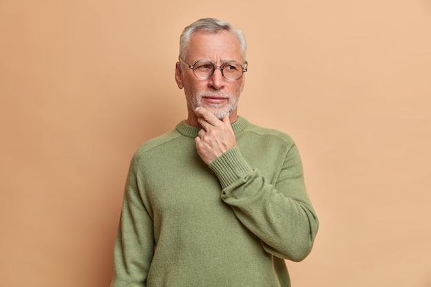 Nadenkend ernstige oude bebaarde man houdt kin vast en kijkt bedachtzaam weg denkt na over ontvangen suggestie overweegt iets overweegt draagt casual trui geïsoleerd over bruine muur
